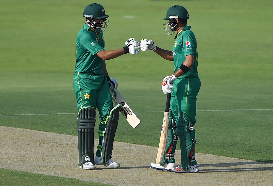 ABU DHABI, UNITED ARAB EMIRATES - OCTOBER 05: Babar Azam (R) of Pakistan celebrates scoring boundary with Azhar Ali (L) during the third One Day International match between Pakistan and West Indies at Zayed Cricket Stadium on October 5, 2016 in Abu Dhabi, United Arab Emirates. (Photo by Tom Dulat/Getty Images)